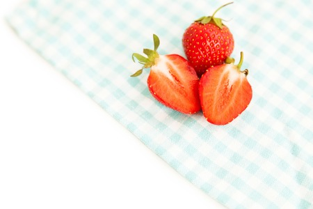 harvest background: Fresh ripe strawberries on a tablecloth as a summer  harvest background isolated on white