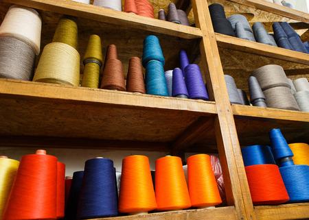 Colored skeins on the shelfs Фото со стока