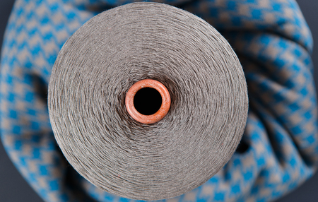 Grey colour skein on the blue and grey textile background