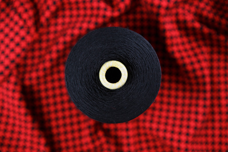Black colour skein on the black and red textile background