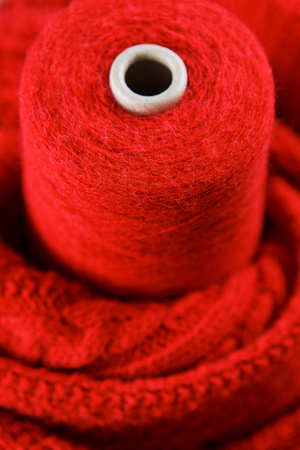 Red color skein on the red textile background