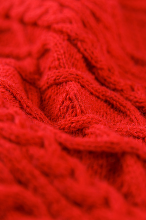 Closeup red color cotton knitted textile with pattern as background