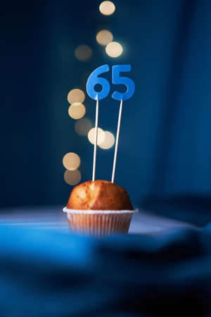 Birthday cupcake or muffin with sixty five (65) number and lights on the blue background. Birthday or anniversary concept