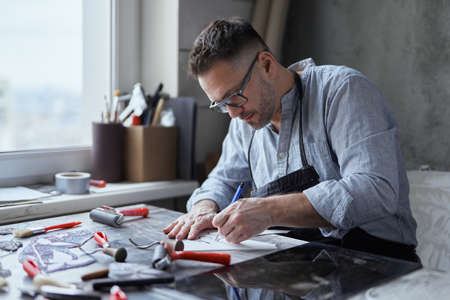 Adorable caucasian bearded man in apron and glasses sitting at the table in studio making linocut with cutting instrument. Making lithography concept. High quality photo Stock Photo