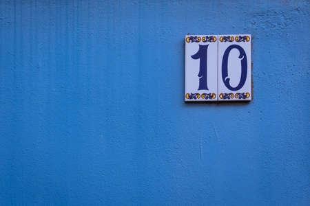 numero diez: Casa número diez en una pared azul Foto de archivo