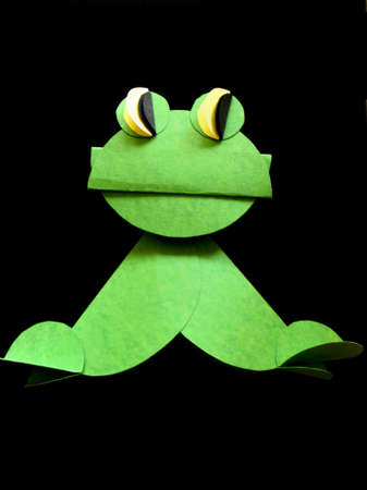 amphibia: One green frog made from paper on the black background. Stock Photo