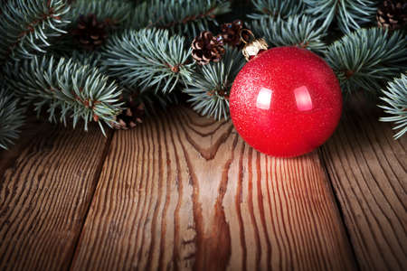 Red christmas ball on wooden background with branches of silver spruce  Copy space  photo
