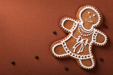 Christmas gingerbread woman with chocolate pills on brown paper background photo