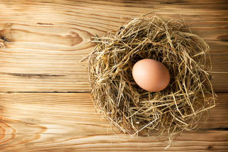 Egg in hay nest on wooden table background. Top view photo
