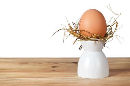 easter nest: Easter egg in hay nest on white stand.