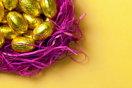 Chocolate easter eggs in pink nest  Holiday background  Top view  Macro shot photo