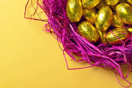 Gold easter eggs in pink nest  Holiday background with sweets  Top view  Macro shot photo