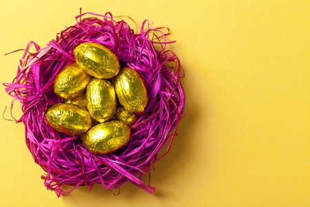 Chocolate easter eggs in pink nest  Holiday composition on yellow paper background  Top view  Macro shot photo