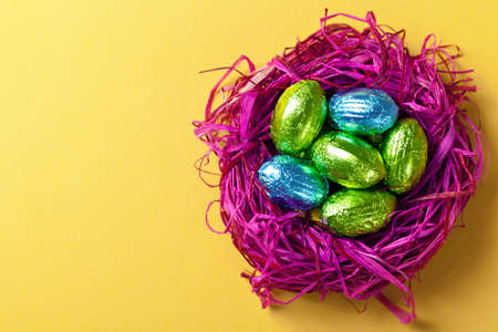 easter nest: Easter eggs in pink nest  Holiday composition on yellow paper background  Top view  Macro shot