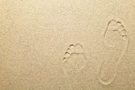sandy feet: Footprints on sandy beach background with copy space