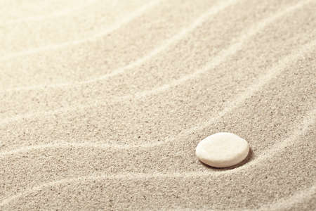 Sand background with white stone. Sandy beach texture