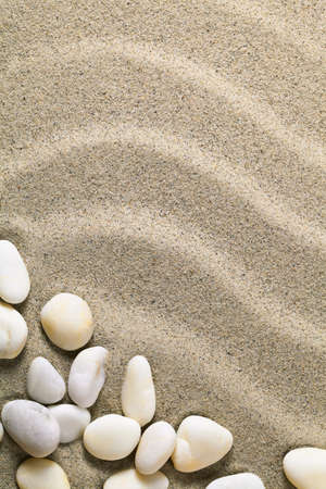 Sand background with stones for summer. Sandy beach texture. Macro shot. Copy space