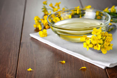 Rapeseed oil with flower of rapeseed. Food composition on wooden table