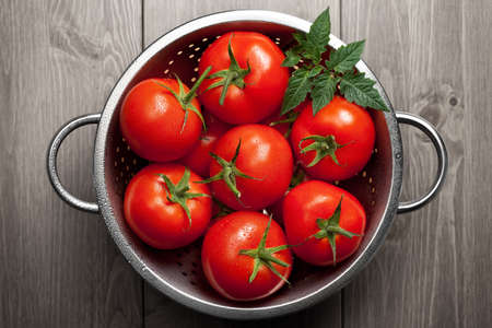 Fresh tomatoes with green leaf and waterdrops in colander on wooden background. Top view