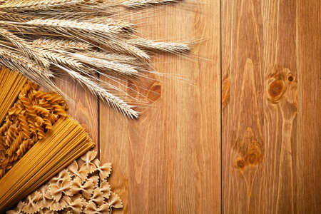 Pasta with wheat ear on wooden background. Different types of whole wheat pasta. Top view. Copy space