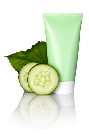 Face mask tube with fresh cucumber slices and leaf on white background. Macro shot