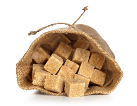 Brown sugar cubes in sack on white background. Macro shot photo