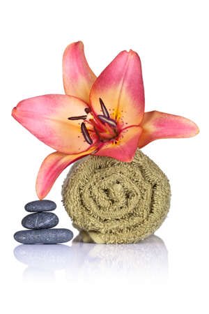Lily, towel and spa stones on white background. Spa concept. Macro shot