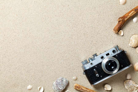 Sand background. Sandy beach texture. Summer concept with old retro camera. Top view