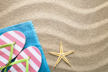 Sand background with towel, flip flops and starfish. Summer concept. Top view