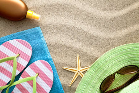 Sandy beach background with towel, flip flops, hat, sun glasses, suntan oil and starfish. Summer concept. Top view