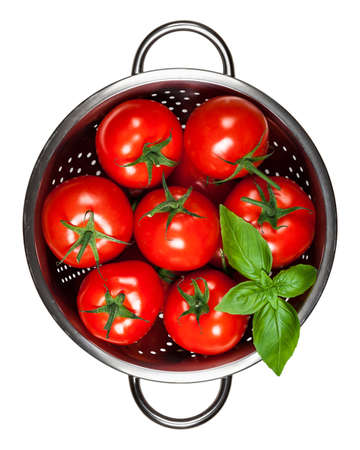 Tomatoes with basil in colander isolated on white background. Top view Stock Photo