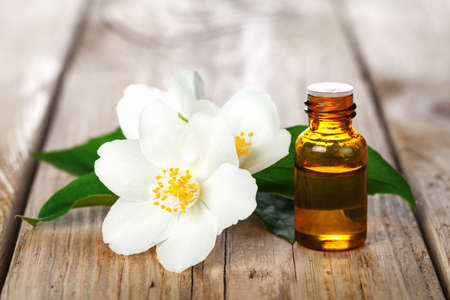 Jasmine essential oil and flowers on wooden table background. Beauty treatment