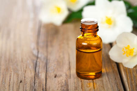 Jasmin essential oil with jasmine flowers on wooden table background. Beauty treatment. Copy space  Stock Photo