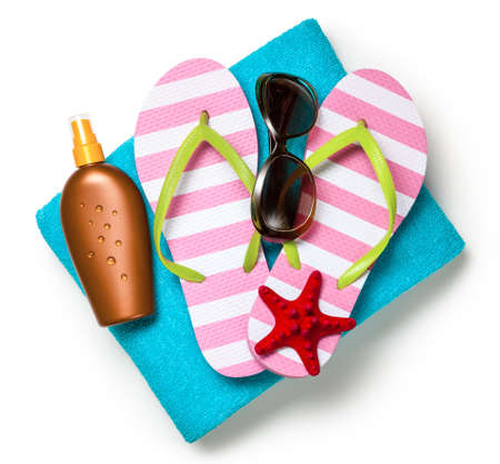 Beach accessories. Flip-flops, towel, sun tan lotion and sunglasses on white background. Top view