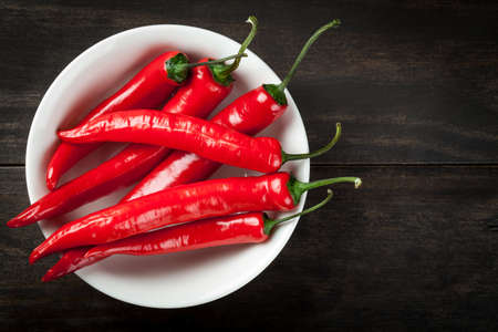 red chilli: Red hot chili peppers on white plate on table background. Copy space. Top view Stock Photo