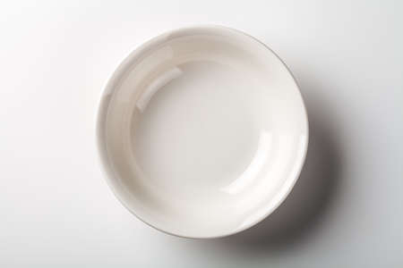 White plate on white background with shadow. Top view