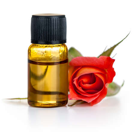 Rose oil in bottle with red rose flower on white background Stock Photo