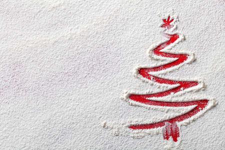 Christmas tree on flour background. White flour looks like snow. Top view photo