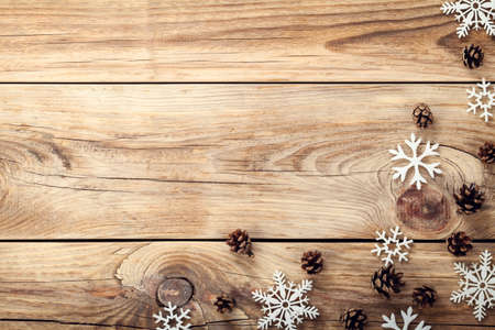 holiday decor: Christmas background with snowflakes and cones on wooden table with copy space Stock Photo