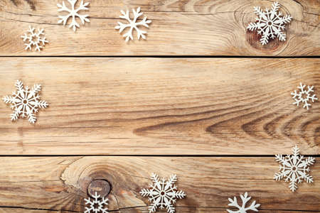 Christmas background with snowflakes on wooden table. Copy space. Top view