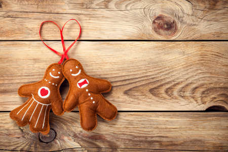 Gingerbread man and woman on wooden table background photo