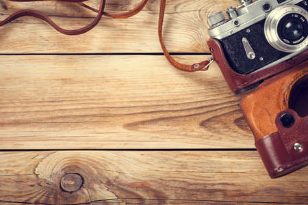 Old retro camera on wooden table background. Copy space. Top view