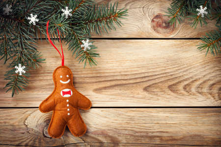 Christmas background with spruce tree and gingerbread man on wooden table. Copy space. Top view photo