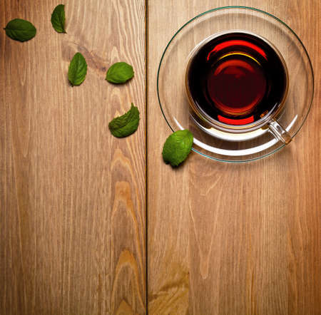 Tea mint in glass cup with fresh mint leaves on wooden background. Top view photo