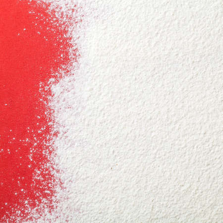 White wheat flour looks like snow on red paper background. Top view. Copy space Banque d'images