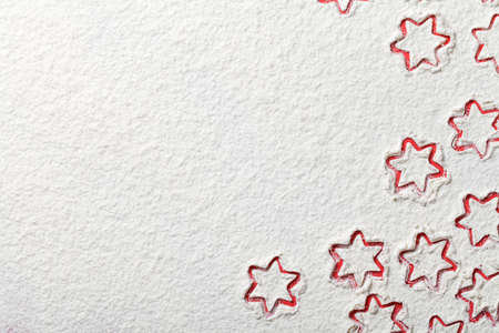 Christmas stars on flour background with copy space. White flour looks like snow. Top view