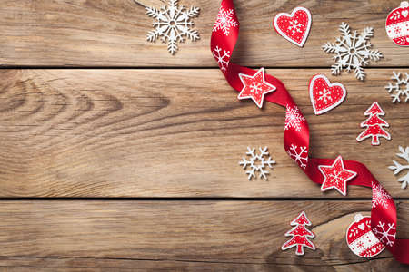 Christmas background with snowflakes and red decoration on wooden table. Copy space. Top view Standard-Bild