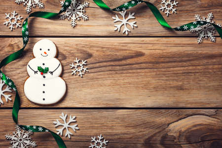Christmas background with gingerbread cookie in shape of snowman on wooden table. Copy space. Top view Stock Photo