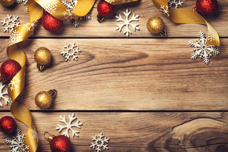 Christmas background with snowflakes, red and gold balls on wooden table. Copy space. Top view