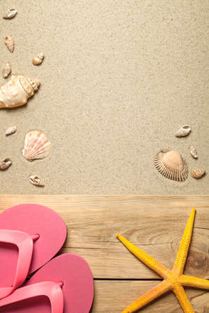 Summer concept with pink flip flops, yellow starfish and shells on sandy beach. Top view